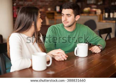 Young handsome man holding hands with his girlfriend while hanging out in a coffee shop - stock photo