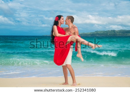 young handsome man holds a beautiful brunette in a red dress on the tropical coast