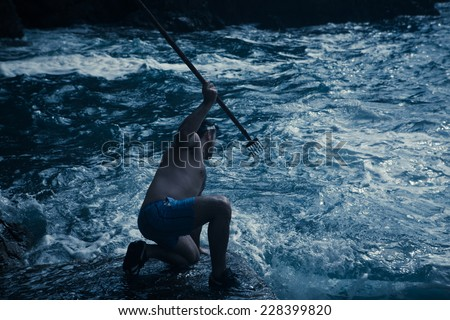 Young handsome man hunting fish the old way. Fishing with spearheads, with snorkel and flippers on. Survival training, extreme sports - stock photo