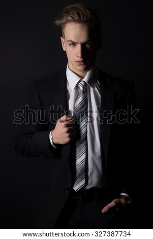 young handsome man in a business suit and a white shirt and tie in formal style in the Studio on a black background - stock photo