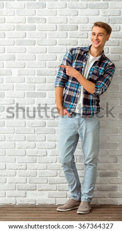 Young handsome man in a checkered shirt and denim pants, keep a hand in his pocket, smiling and looking at the camera, standing on the brick wall background