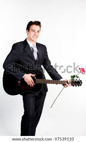 Young handsome man in a dark business suit, sings and plays guitar - stock photo