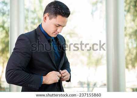 Young handsome man in a suit buttoning his jacket and getting ready for a meeting at work - stock photo