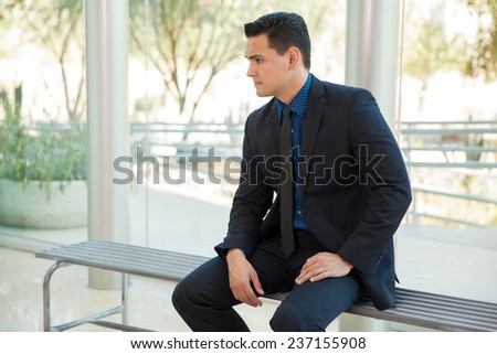 Young handsome man in a suit sitting and waiting for his turn for a job interview - stock photo