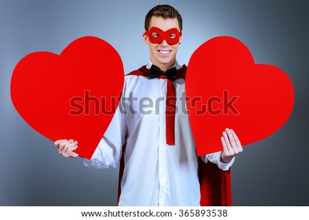 Young handsome man in a superhero costume holding a red hearts. Love concept. Valentine's Day. - stock photo