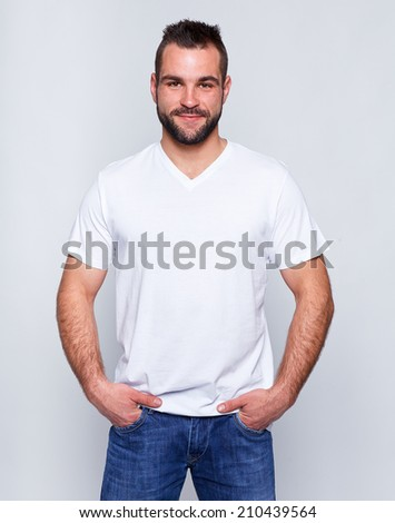 Young handsome man in a white t-shirt on gray background - stock photo