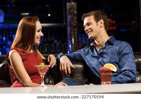 Young handsome man in bar accompanied by elegant lady - stock photo