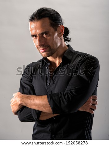 Young handsome man in black shirt on a gray background - stock photo