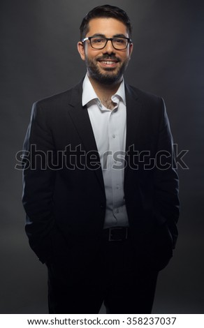 Young handsome man in black suit and glasses on grey