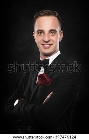 Young handsome man in black suit on dark background. - stock photo