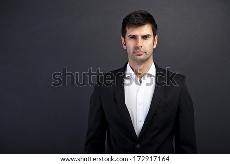 Young handsome man in black suit smiling on dark background