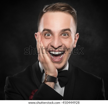 Young handsome man in black suit smiling on dark background. - stock photo