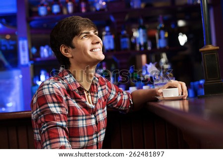 Young handsome man in casual sitting at bar