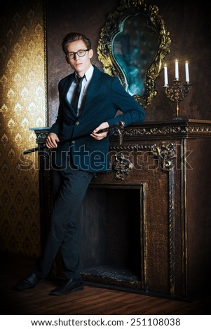 Young handsome man in elegant suit stands by the fireplace in a room with classic vintage style. Fashion. - stock photo