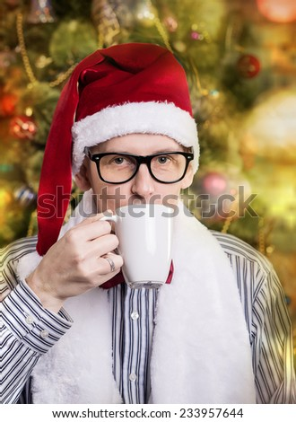 young handsome man in Santa caps with focus on mug - stock photo