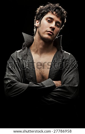young handsome man in shirt against black background - stock photo