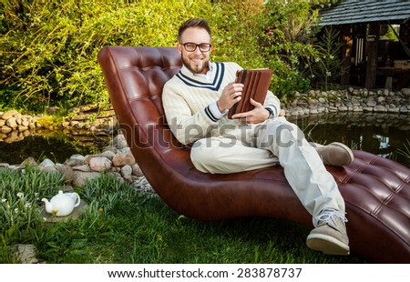 Young handsome man in sit in luxury sofa with iPad in summer garden.