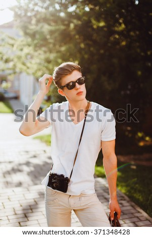 young handsome man in stylish sunglasses and fashionable clothes posing on the street with travel bag, vintage retro camera Nikon, outdoor portrait, close up - stock photo