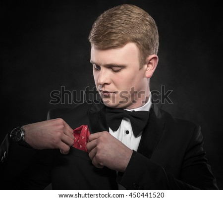 Young handsome man in suit with bow-tie adjusts his handkerchief on dark background. - stock photo