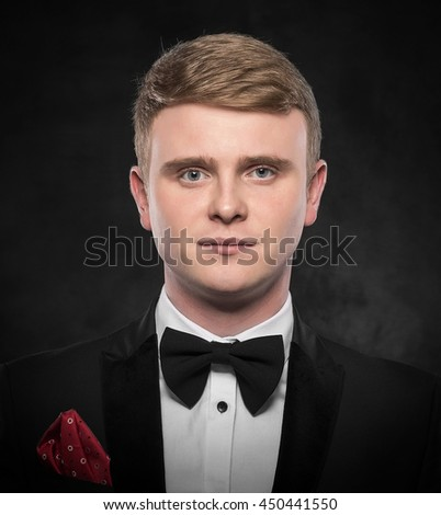 Young handsome man in suit with bow-tie on dark background. - stock photo
