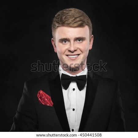 Young handsome man in suit with bow-tie smiling on dark background. - stock photo