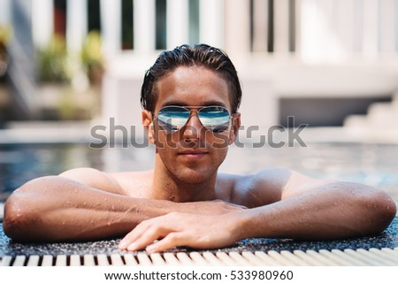 Young handsome man in sunglasses posing in swimming pool