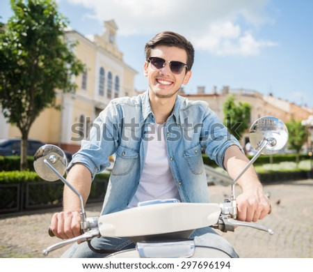 Young handsome man in sunglasses riding scooter. Front view. - stock photo