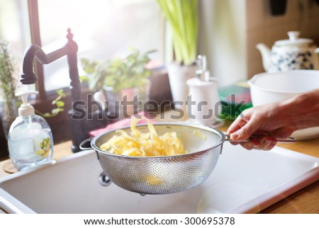 Young handsome man in the kitchen preparing tagliatelle   - stock photo
