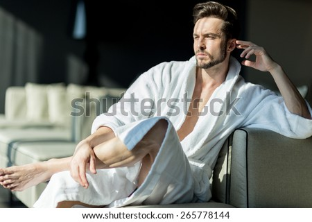 Young, handsome man in the morning thinking while sitting in a hotel room in a robe - stock photo
