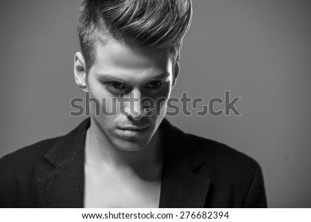 Young handsome man in tuxedo posing in the studio. Black and white fashion portrait.
