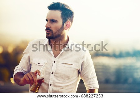 Young handsome man is drinking beer and an enjoying sunset.