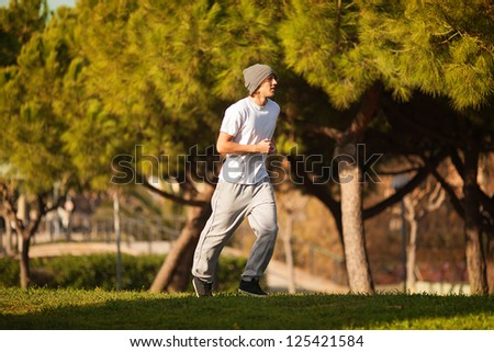 young handsome man jogging in public park - stock photo