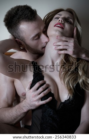 Young handsome man kissing his sexy woman's neck