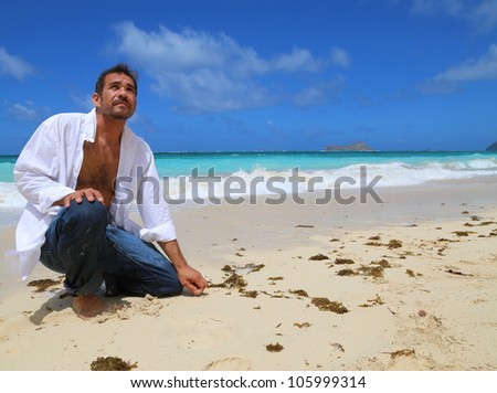 Young handsome man kneeling by the beach looking up at sky - stock photo