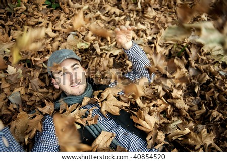 Young handsome man laying on autumn leaves. - stock photo