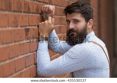 Young handsome man leaning on a brick wall. Fashion