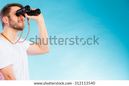 Young handsome man lifeguard on duty or tourist looking through binocular studio shot on blue - stock photo