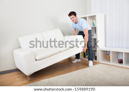 Young Handsome Man Lifting Couch In Living Room - stock photo
