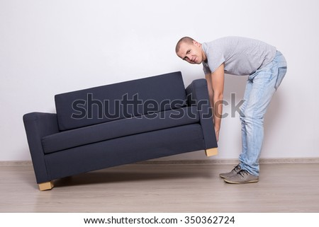 young handsome man lifting up sofa or couch - stock photo