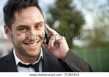 Young handsome man looking at his phone - stock photo