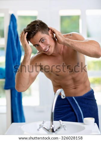 Young handsome man looking at self in bathroom mirror - stock photo