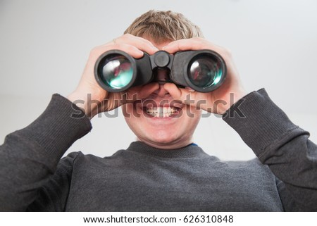 Young handsome man looking through window with binocular glasses. Male person on balcony