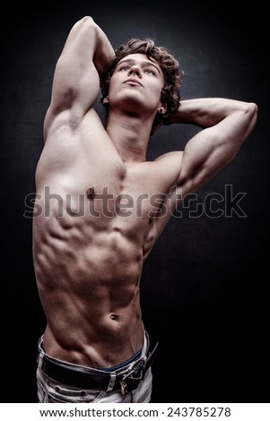 Young handsome man looking up and stretching - stock photo