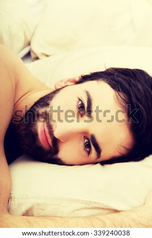 Young handsome man lying in bed.