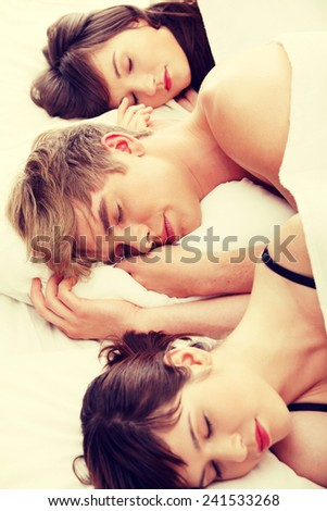 Young handsome man lying in bed with two girls