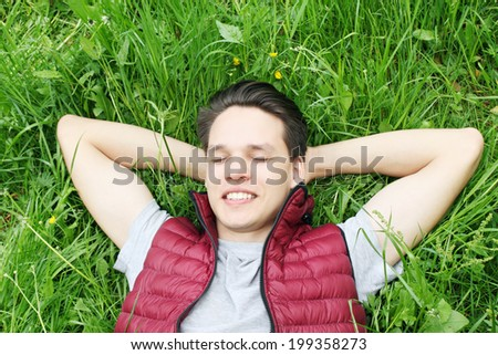 Young handsome man lying on the grass