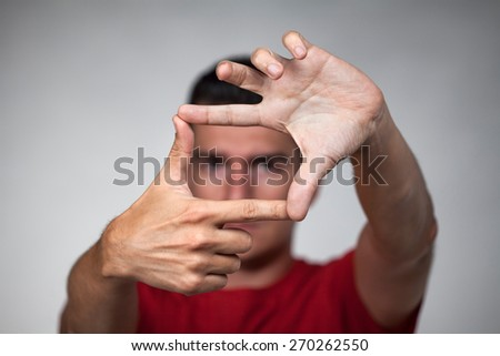 Young handsome man makes frame with his fingers