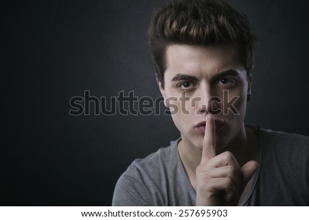 Young handsome man making silence gesture and looking at camera