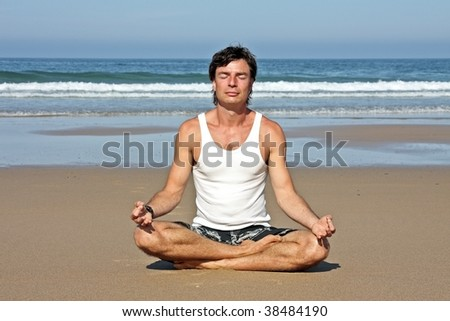 Young handsome man meditating on the beach sitting in lotus position - stock photo