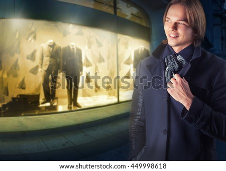 Young handsome man on a background of night shop windows - stock photo